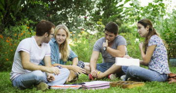 Group of young friends studying in park